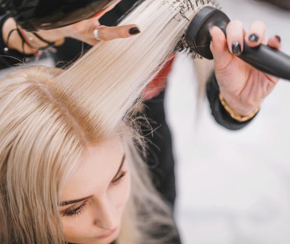 Mulher loira fazendo escova no cabelo