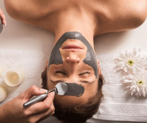 Mulher limpando o rosto com argila