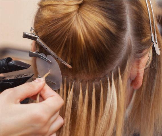 Mulher loira aplicando mega hair